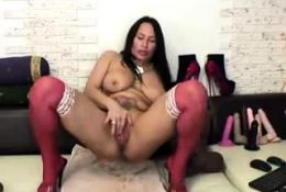Mature tattooed lady in red stockings plays with her sex