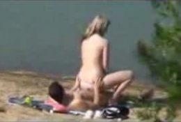 Elle lui taille une pipe sur la plage